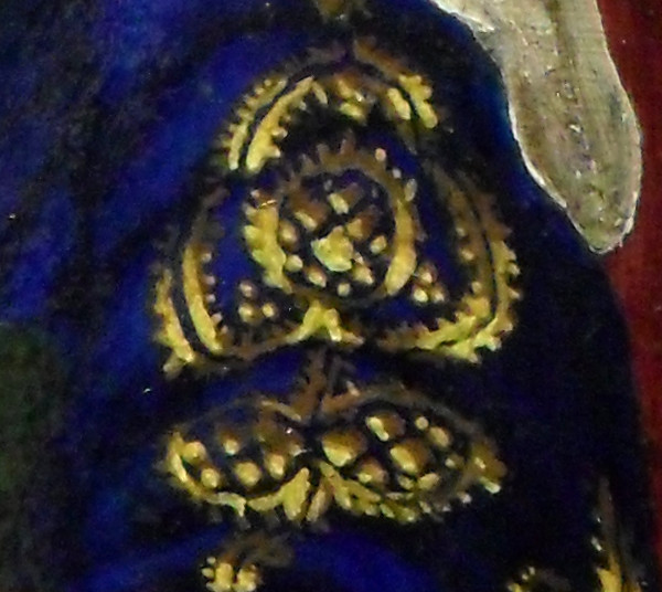 Detail of the blue and gold brocade on the top of her left sleeve. As was often the case, the material that made the clothes was cut so that patterns were symmetrical. At the top, you can see the end of the fine linen headdress hanging down. Copyright (c)2016 Paul Alan Grosse