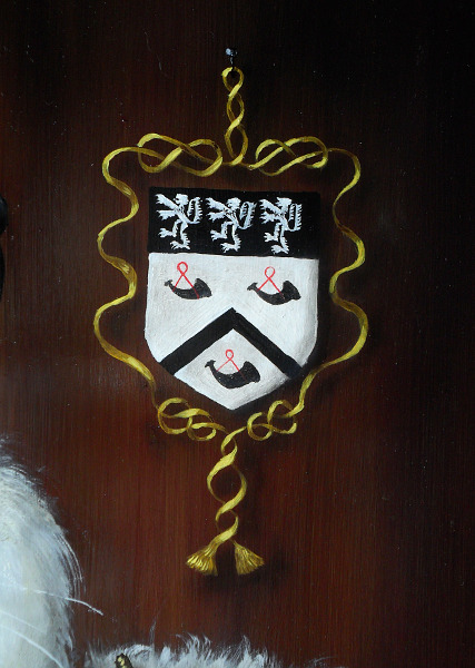 The Hinksman coat of arms, surrounded by a golden ribbon that ends with golden tassels, suspended by a small black nail. Devices were used a lot in paintings to allow something abstract, such as the coat of arms, to exist within the boundary of the painting where everything else has to conform to the restrictions of 'being real.' Copyright (c)2016 Paul Alan Grosse